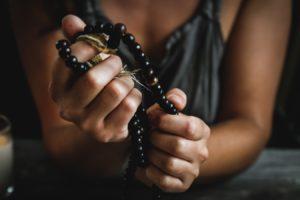 Une femme tient un chapelet ou collier de prière