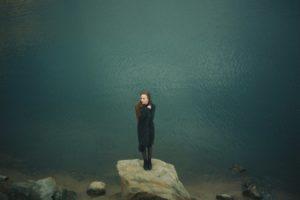 Devant le lac, fille peu heureuse